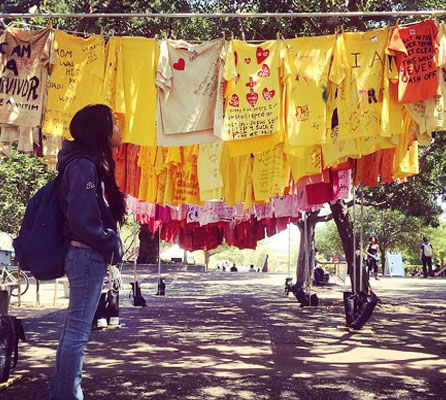 student looking at messages from sexual assault survivors written on t-shirts hanging on a clothesline