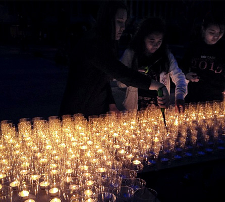 Nighttime photo with a tabletop covered in lit tealight candles and a few students lighting candles.