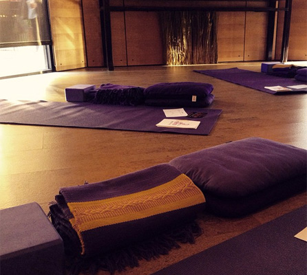 Yoga mats, blankets, and cushions spread out around a yoga studio.